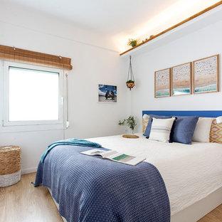 Imagen de dormitorio principal, marinero, de tamaño medio, sin chimenea, con paredes blancas, suelo de madera clara y suelo marrón