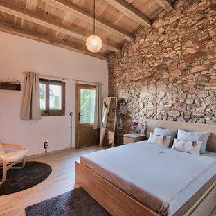 Modelo de dormitorio rústico, sin chimenea, con paredes blancas y suelo de madera clara