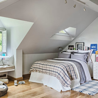 Example of a mid-sized classic master medium tone wood floor bedroom design in Madrid with white walls and no fireplace
