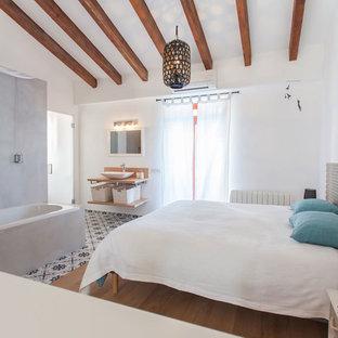 Ejemplo de dormitorio principal, mediterráneo, de tamaño medio, con paredes blancas, suelo de madera en tonos medios y suelo marrón