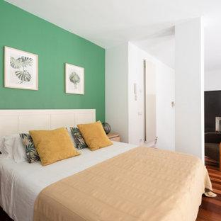 Modelo de dormitorio tipo loft, contemporáneo, con paredes verdes, suelo de madera oscura y suelo marrón