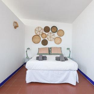 Imagen de dormitorio tipo loft, costero, de tamaño medio, sin chimenea, con paredes blancas, suelo de baldosas de terracota y suelo rojo