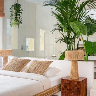 Modelo de dormitorio tropical con paredes beige, suelo de madera oscura y suelo marrón