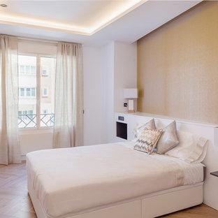 Diseño de habitación de invitados actual con paredes blancas, suelo de madera en tonos medios y suelo marrón