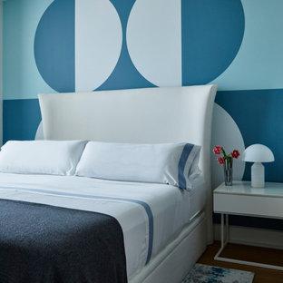 Foto de dormitorio contemporáneo con paredes azules, suelo de madera en tonos medios y suelo marrón
