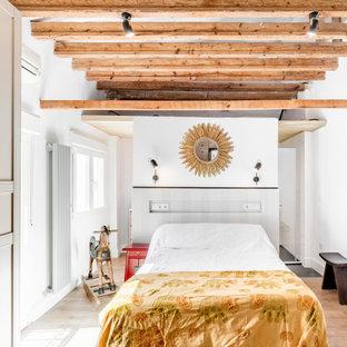Diseño de dormitorio mediterráneo con paredes blancas, suelo de madera en tonos medios y suelo marrón