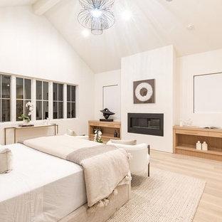 ロサンゼルスの大きいコンテンポラリースタイルのおしゃれな主寝室 (白い壁、淡色無垢フローリング、吊り下げ式暖炉、木材の暖炉まわり、ベージュの床) のレイアウト