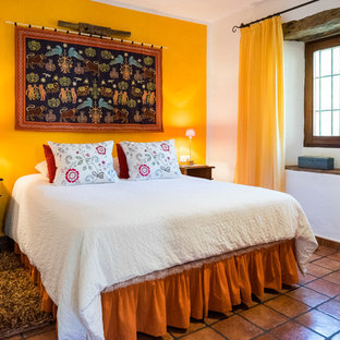 Example of a mid-sized tuscan master terra-cotta tile bedroom design in Malaga with yellow walls and no fireplace