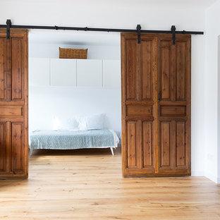 Modelo de dormitorio principal, escandinavo, de tamaño medio, sin chimenea, con paredes blancas, suelo de madera clara y suelo beige