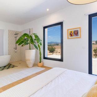 Imagen de dormitorio principal, mediterráneo, sin chimenea, con paredes blancas, suelo de madera clara y suelo beige