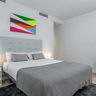 Foto de dormitorio escandinavo con paredes grises y suelo de madera clara