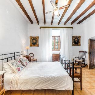 Неиссякаемый источник вдохновения для домашнего уюта: большая хозяйская спальня в стиле кантри с белыми стенами и полом из терракотовой плитки без камина