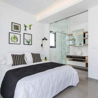 Diseño de dormitorio contemporáneo con paredes blancas y suelo gris