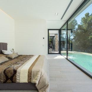Ejemplo de dormitorio moderno con paredes blancas, suelo de madera clara y suelo beige
