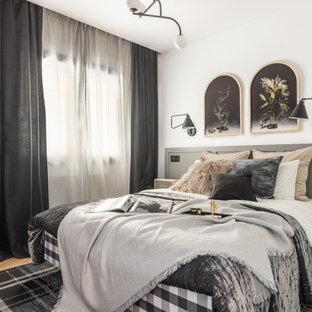Modelo de dormitorio escandinavo con paredes blancas, suelo de madera en tonos medios y suelo marrón