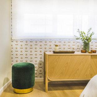 Modelo de dormitorio principal, escandinavo, grande, sin chimenea, con paredes beige, suelo de madera en tonos medios y suelo marrón