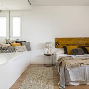 Ejemplo de dormitorio principal, actual, grande, sin chimenea, con paredes blancas y suelo de madera en tonos medios