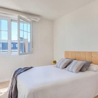 Imagen de dormitorio escandinavo con paredes blancas, suelo de madera clara y suelo beige