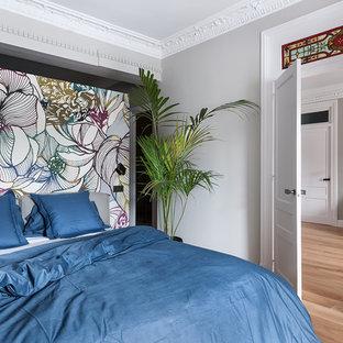 Ejemplo de dormitorio ecléctico, de tamaño medio, con paredes grises, suelo de madera en tonos medios y suelo marrón