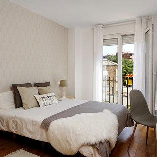 Modelo de dormitorio principal, clásico renovado, con paredes blancas, suelo de madera en tonos medios y suelo marrón
