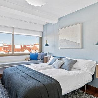Imagen de dormitorio principal, actual, de tamaño medio, sin chimenea, con paredes azules, suelo de madera oscura y suelo marrón