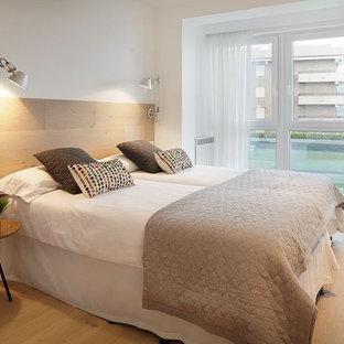 Imagen de habitación de invitados mediterránea, de tamaño medio, sin chimenea, con paredes blancas y suelo de madera clara