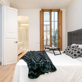 Modelo de dormitorio contemporáneo con paredes blancas, suelo de madera clara y suelo beige