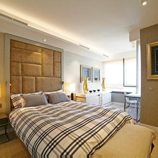 Diseño de dormitorio actual con suelo de madera clara, paredes grises y suelo beige