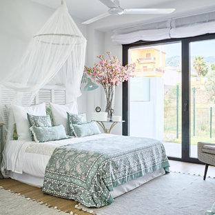 Imagen de dormitorio principal, marinero, de tamaño medio, con paredes blancas y suelo de baldosas de porcelana