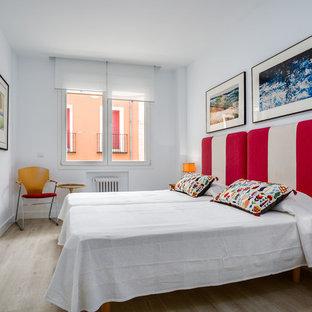 Ejemplo de habitación de invitados bohemia con paredes blancas, suelo de madera clara y suelo beige