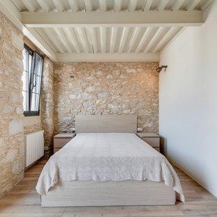 Diseño de dormitorio principal, de estilo de casa de campo, de tamaño medio, sin chimenea, con paredes beige y suelo de madera clara