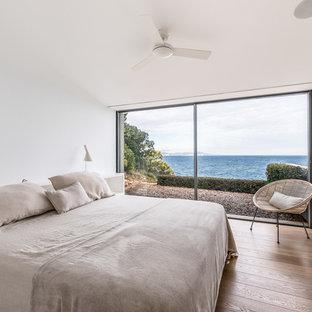 Modelo de dormitorio marinero con paredes blancas, suelo de madera en tonos medios y suelo marrón