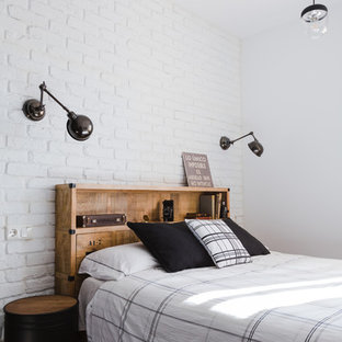 This is an example of an urban master bedroom in Malaga with white walls and dark hardwood flooring.