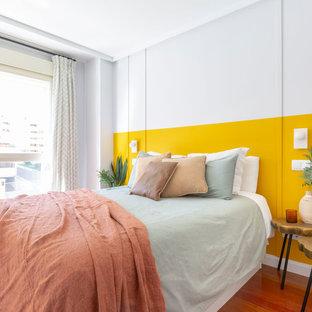 Foto de habitación de invitados actual con paredes amarillas y suelo de madera en tonos medios