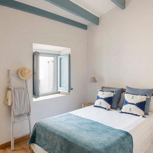 Imagen de dormitorio principal, mediterráneo, de tamaño medio, sin chimenea, con paredes blancas, suelo de madera en tonos medios y suelo marrón