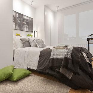 Ispirazione per una camera matrimoniale minimalista di medie dimensioni con pareti bianche, parquet chiaro e pavimento giallo