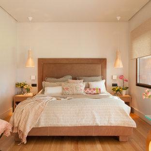 Modelo de dormitorio principal, clásico renovado, de tamaño medio, sin chimenea, con paredes blancas, suelo de madera en tonos medios y suelo marrón