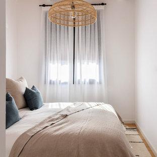 Diseño de dormitorio abovedado, mediterráneo, con paredes blancas, suelo de madera en tonos medios y suelo marrón