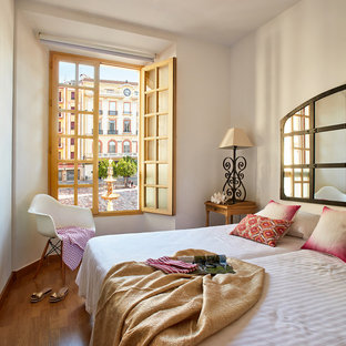 Modelo de habitación de invitados mediterránea, de tamaño medio, sin chimenea, con paredes blancas y suelo de madera en tonos medios