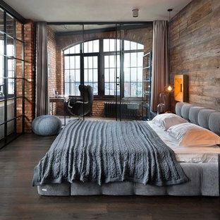 Photo of an industrial master bedroom in Other with brown walls, dark hardwood floors and brown floor.