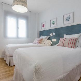 Foto de dormitorio costero con paredes blancas, suelo de madera en tonos medios y suelo marrón