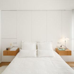 Ejemplo de dormitorio escandinavo, sin chimenea, con paredes blancas y suelo de madera clara
