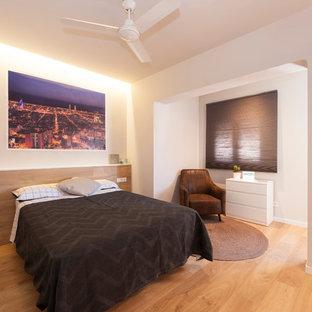 Diseño de dormitorio principal, contemporáneo, grande, con paredes grises, suelo de madera clara y suelo marrón