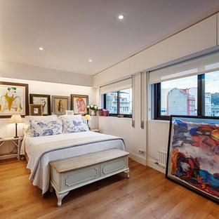 Ejemplo de dormitorio clásico renovado, de tamaño medio, con paredes blancas y suelo de madera en tonos medios