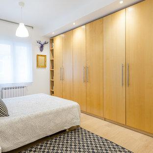 Ejemplo de dormitorio principal, contemporáneo, con paredes blancas, suelo de madera clara y suelo beige