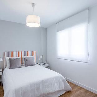 Imagen de habitación de invitados nórdica, pequeña, con paredes grises, suelo de madera en tonos medios y suelo marrón