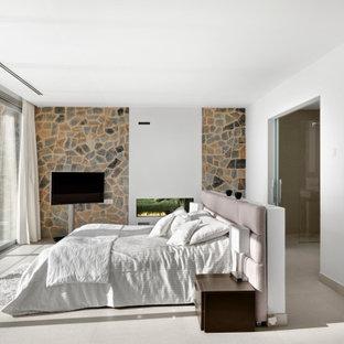 Foto de dormitorio principal, contemporáneo, grande, con paredes blancas, suelo de baldosas de porcelana, chimenea lineal, marco de chimenea de yeso y suelo beige