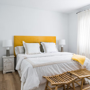 Inspiration for a scandinavian bedroom in Other with white walls, medium hardwood floors and brown floor.