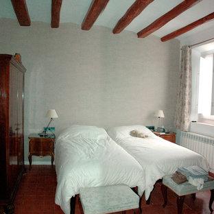 Modelo de dormitorio principal con paredes grises, suelo de baldosas de terracota y suelo rojo