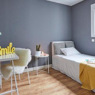 Diseño de dormitorio nórdico con paredes azules, suelo de madera en tonos medios y suelo marrón